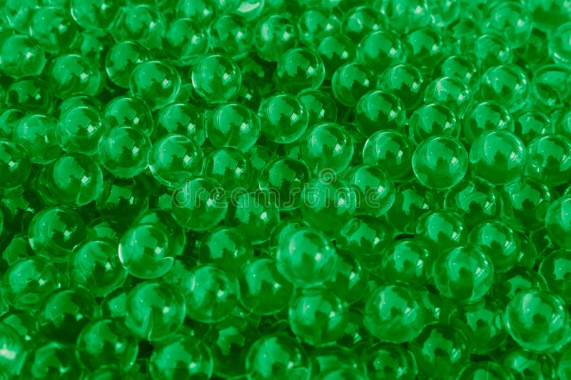 Water green gel balls with bokeh. Polymer gel. Silica gel. Balls of green hydrogel. Crystal liquid ball with reflection. Green stock images