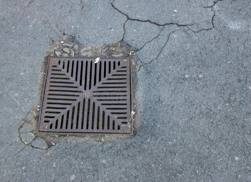 Water Grid outside. A square metal water drain grid set in cracked tarmac stock images