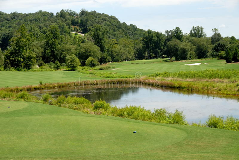 Water hazard on golf course. Scenic view of water hazard or lake on picturesque golf course with forest in background, Georgia, U.S.A royalty free stock image