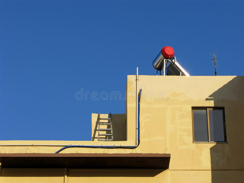 Water heater with solar battery. Modern water heater with solar battery on roof. Clear blue sky stock photography