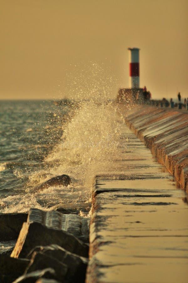 Water het bespatten op een pijler met een boot op achtergrond stock afbeelding