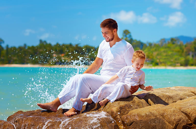 Water het bespatten op lachende vader en zoon stock fotografie