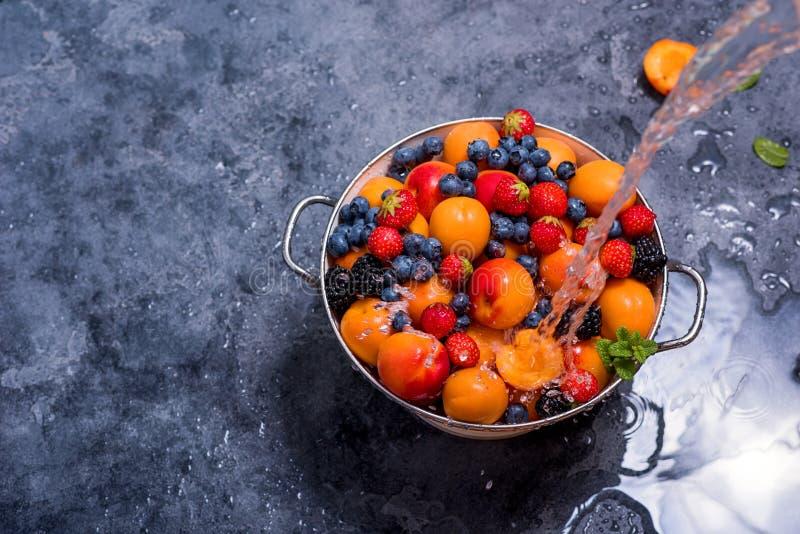 Water het bespatten op verse de zomervruchten en bessen, abrikozen, bosbessen, aardbeien in vergiet, wassende vruchten en bessen, stock foto's