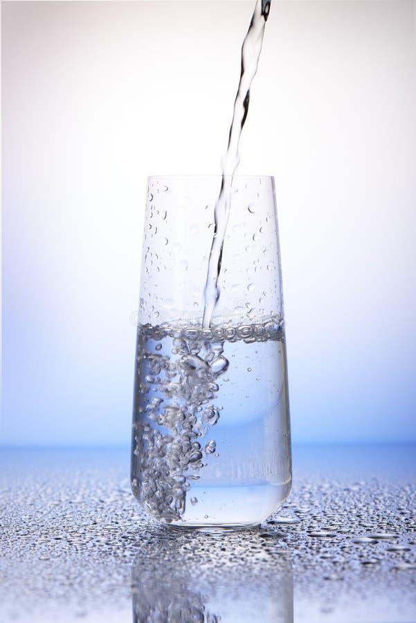 Water het gieten in helft-gevuld het drinken glas in dalingen van water stock foto's