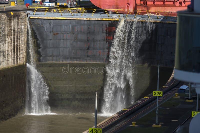 Water het gieten over de sluisdeuren als schip leidt uit het Miraflores-Kanaal van Slotenpanama royalty-vrije stock fotografie