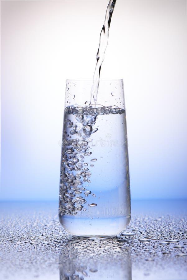 Water het gieten in tweederden volledig het drinken glas royalty-vrije stock foto