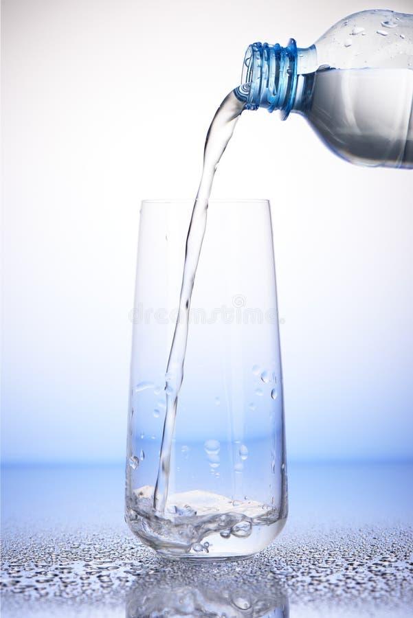 Water het gieten van fles in het drinken van glas op dalingen royalty-vrije stock foto's