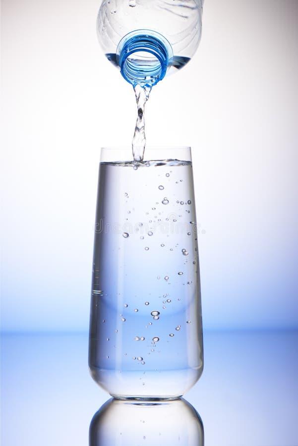 Water het gieten van plastic fles in volledig het drinken glas stock foto's