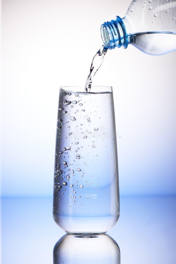 Water het gieten van plastic fles in volledig het drinken glas royalty-vrije stock fotografie