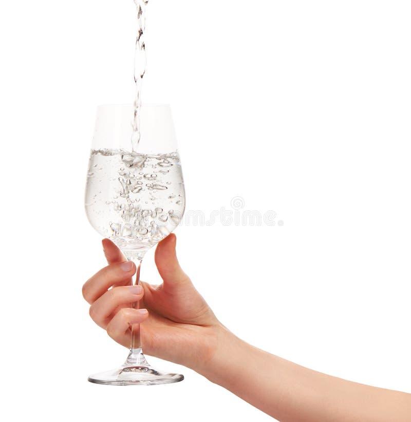 Water het gieten in volledig wijnglas in de hand van de vrouw royalty-vrije stock afbeelding
