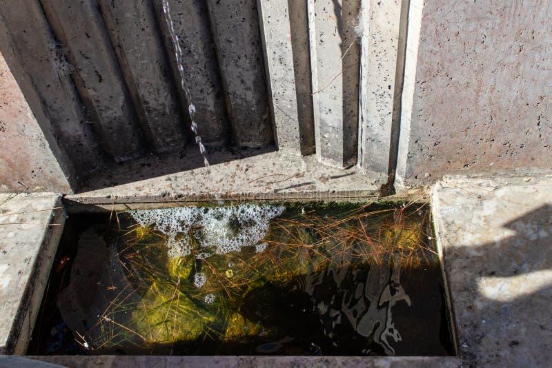Water het uitgieten van marmeren waterkraan stock afbeelding