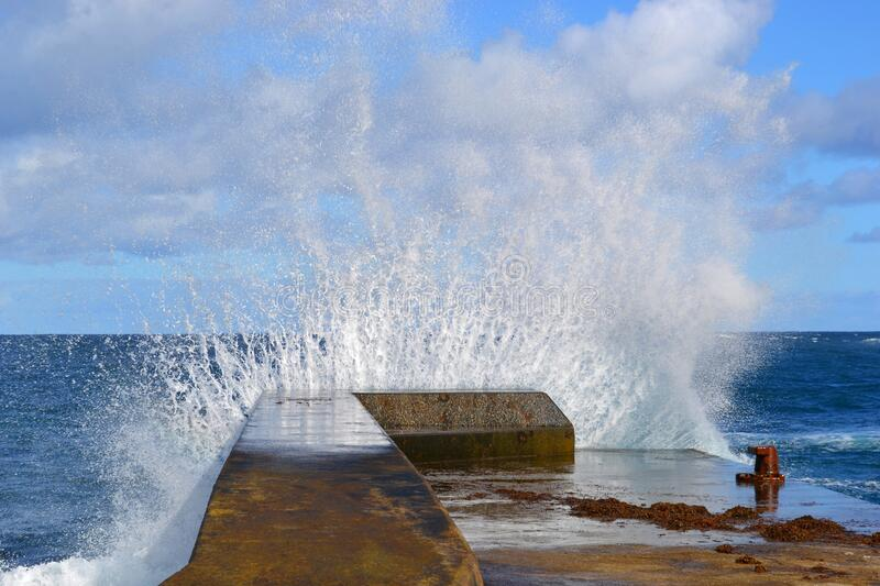 The water hit the concrete pier, the Atlantic Ocean wave, the wild sea, the Azores stock photo