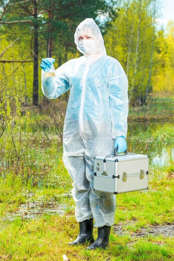 Water intake for research in the laboratory, environmentalist in protective clothing at a water source. In the forest stock photo