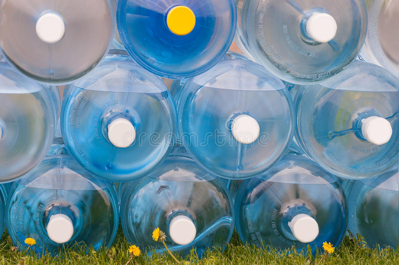 Water Jugs Stacked on Grass. Three rows of jugs full of water stock photography