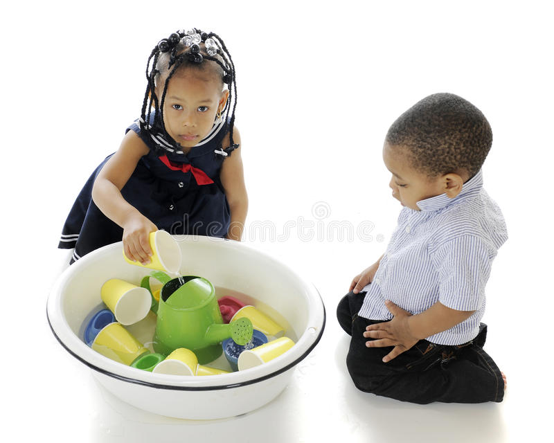 Water, Kids and Toys. An overhead view of two adorable siblings playing in a bucket of water and toys. On a white background royalty free stock images