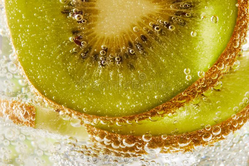 Water with kiwi slices and bubbles. Close up of water with kiwi slices and bubbles stock image