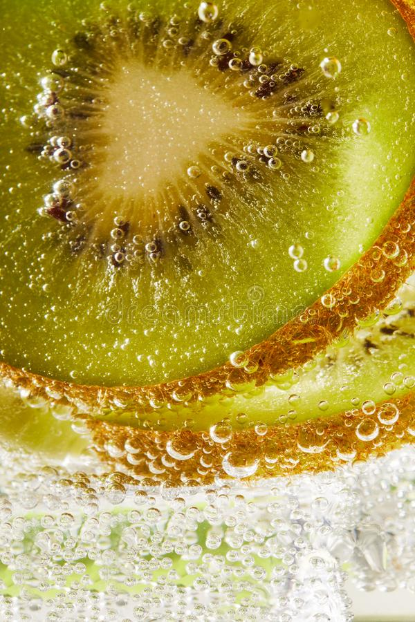 Water with kiwi slices and bubbles. Close up of water with kiwi slices and bubbles royalty free stock image