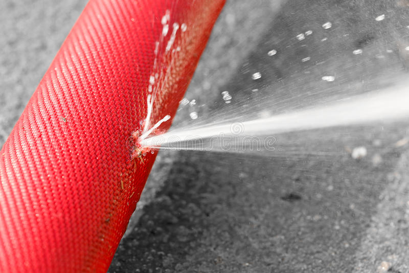 Water leaking from hole in a hose. Water leaking from hole in a industrial hose royalty free stock photos