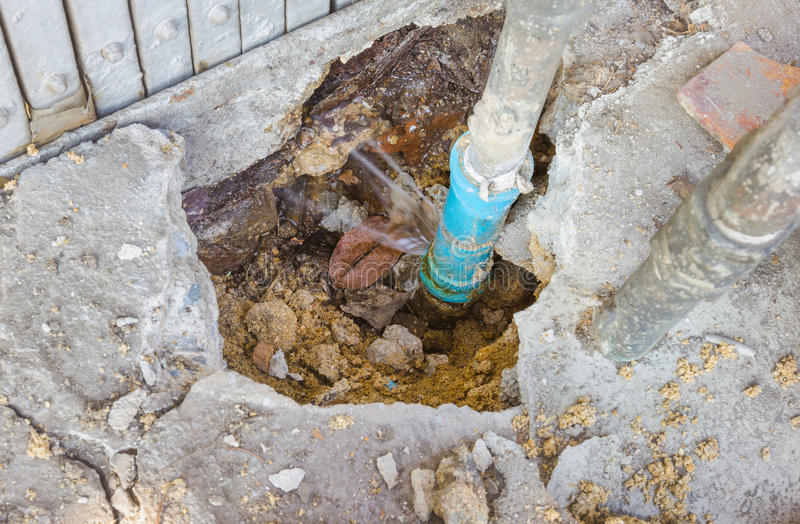 Water leaks from underground blue pipes stock photography