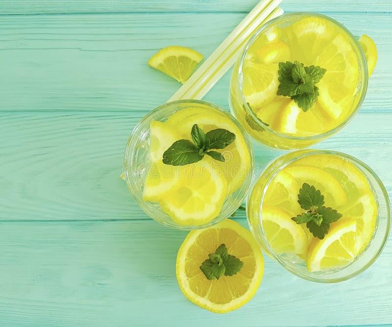 Water soda lemon tube citrus cool refreshment , freshness homemade health mint summer on a blue wooden background. Water lemon antioxidant mint blue wooden royalty free stock photography