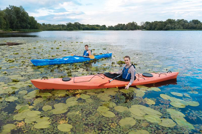 Young man and woman noticing many water lilies while kayaking. Water lilies. Young men and women noticing many water lilies while kayaking in the river on stock photos