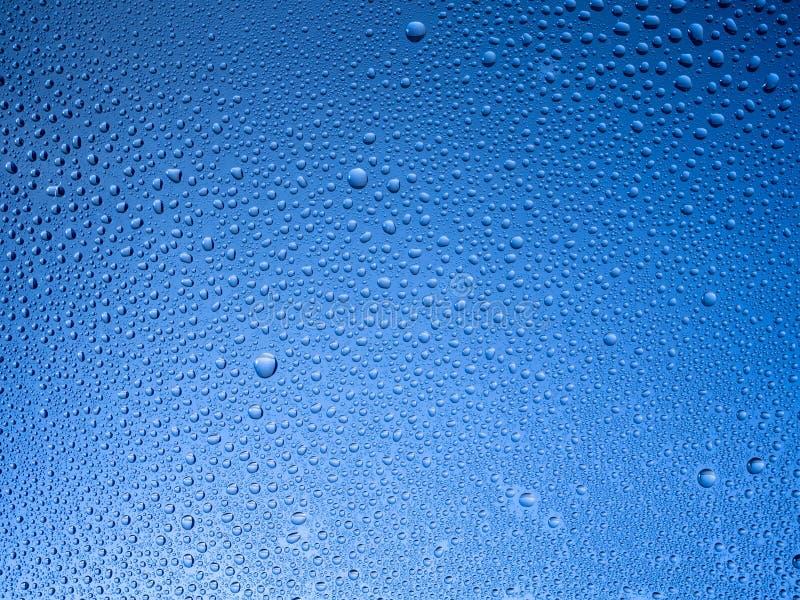 Water liten droppe p? exponeringsglaset med en kul?r bakgrund arkivfoto