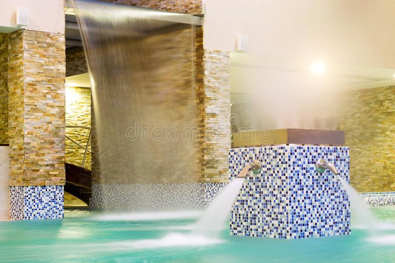 Water massage, stream water in pool. SPA-relaxing. Water massage, stream of clear blue water under pressure flows into pool. SPA-relaxing in warm bubble bath stock images