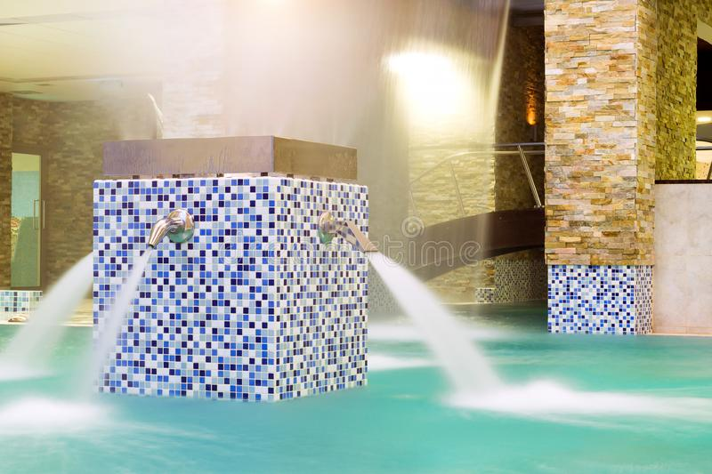 Water massage, stream water in pool. SPA-relaxing. Water massage, stream of clear blue water under pressure flows into pool. SPA-relaxing in warm bubble bath stock photography