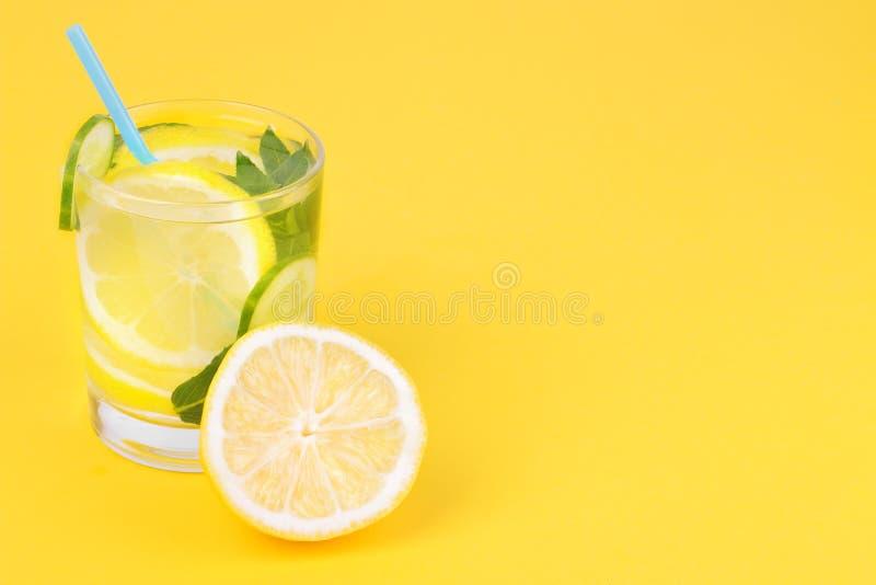 Water met citroen en komkommer en munt in een glaskop naast verse citroen op een heldere gele document achtergrond stock afbeelding