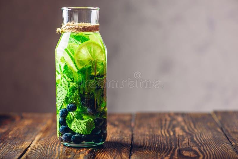 Water met Kalk, Munt en Bosbes op smaak die wordt gebracht die royalty-vrije stock afbeeldingen