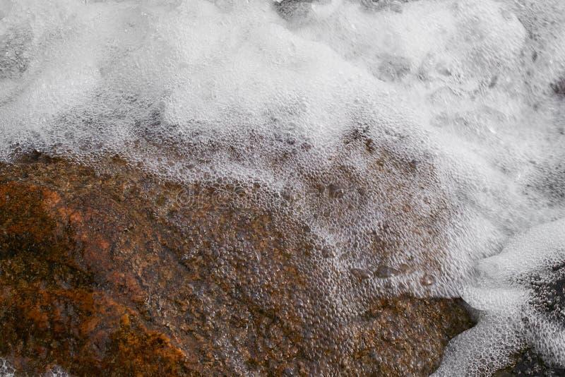 Water met schuimonderbrekingen op de steen stock fotografie