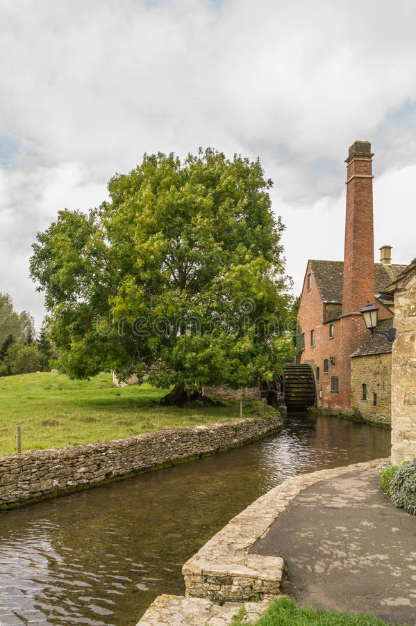 Water mill at Lower Slaughter, Gloucestershire. Water mill and stream at Lower Slaughter, Gloucestershire stock photo