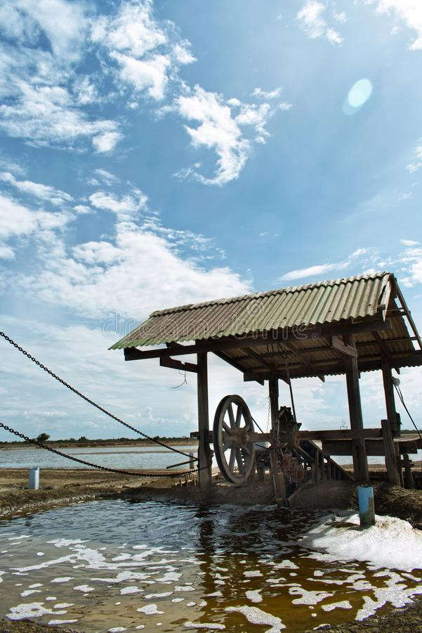 Wind powered wooden turbine pumping sea warter into salt farm in Thailand stock photos