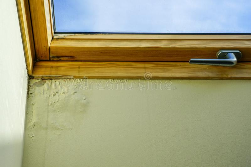 Water and moisture damaged ceiling next to roof window. Water and moisture damaged ceiling next to wooden roof window royalty free stock photography