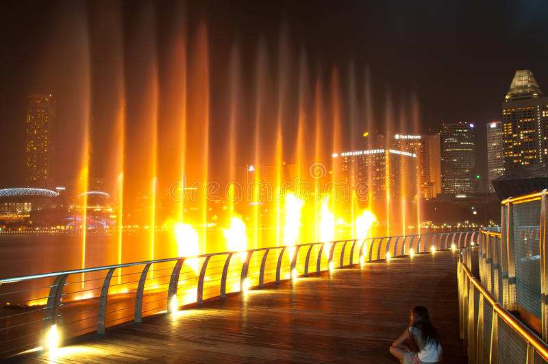 Water Musical Performance. A little girl watching water and fire musical performance at waterfront of Marina Bay Sands. The picture was taken on 08 April 2011 stock photography