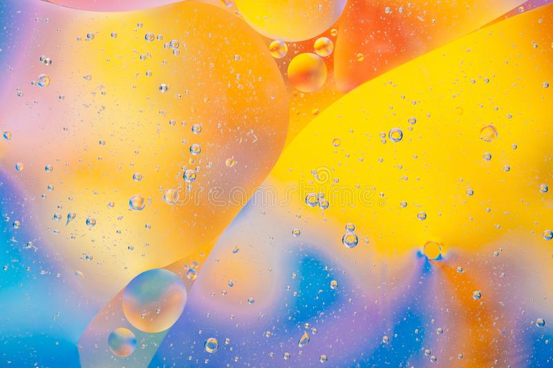 Water oil bubble macro abstract background flow liquid blue aqua yellow pink red colors stock photo