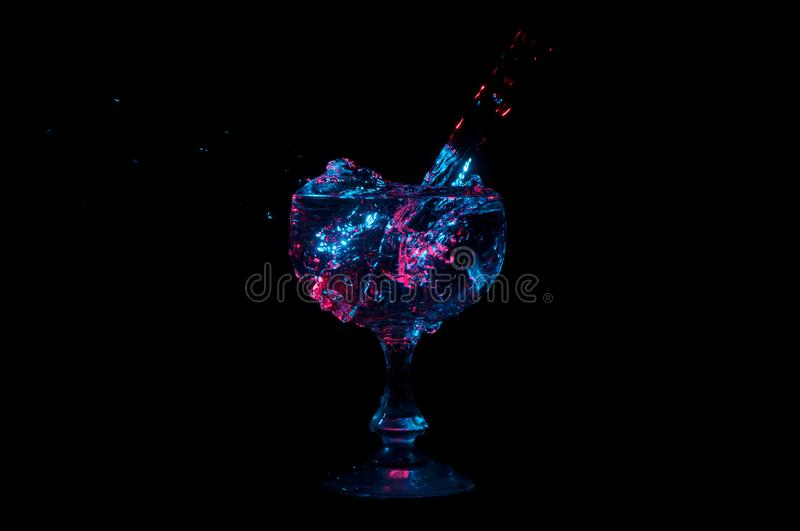 Water overflowing into cup under colorful lights on a black background stock image