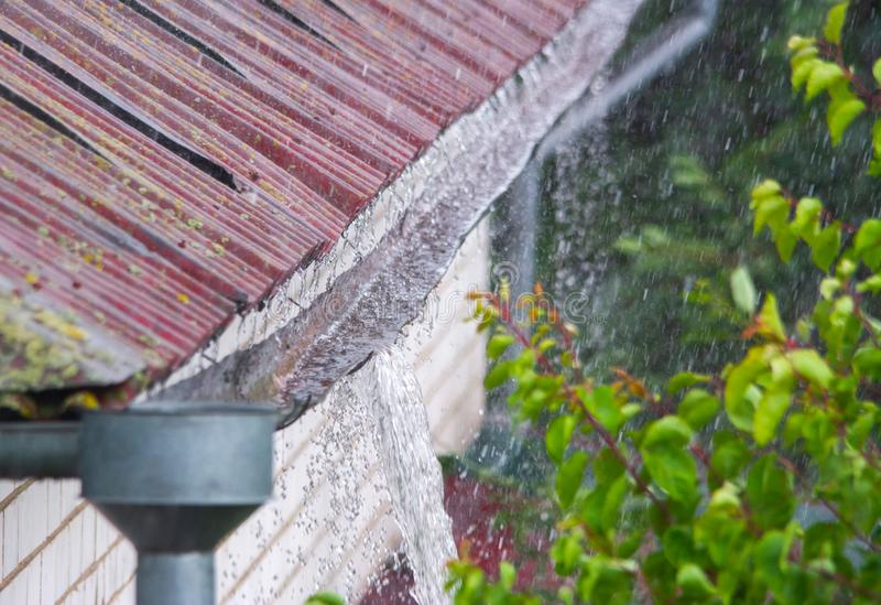 Water overflowing from damaged rain gutter during heavy rainstorm stock images
