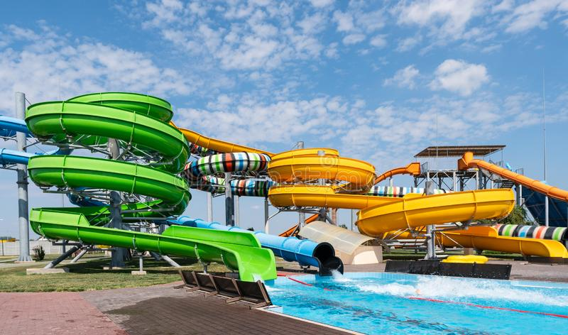 Water park, bright multi-colored slides with a pool. A water park without people on a summer day with a beautiful, cloudy blue sky stock images