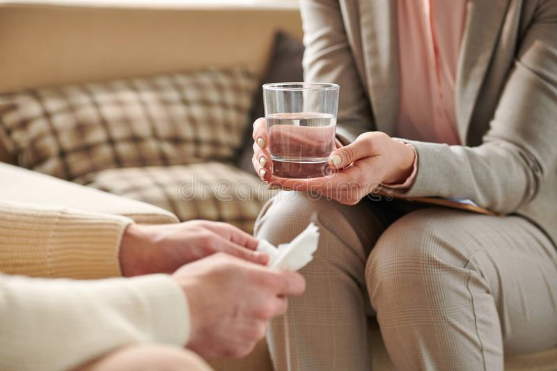 Water for patient. Young female counselor in grey suit holding glass of water for patient while listening to his story royalty free stock photo