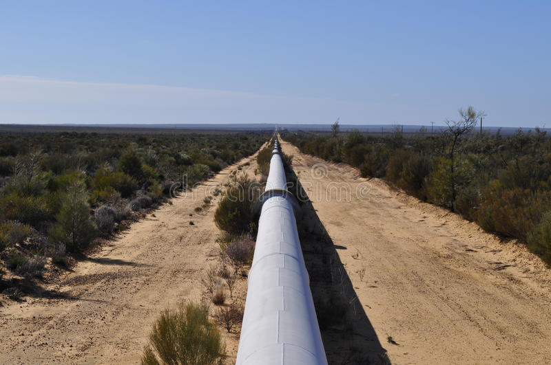 Water gas pipeline into the horizon in australian outback stock images