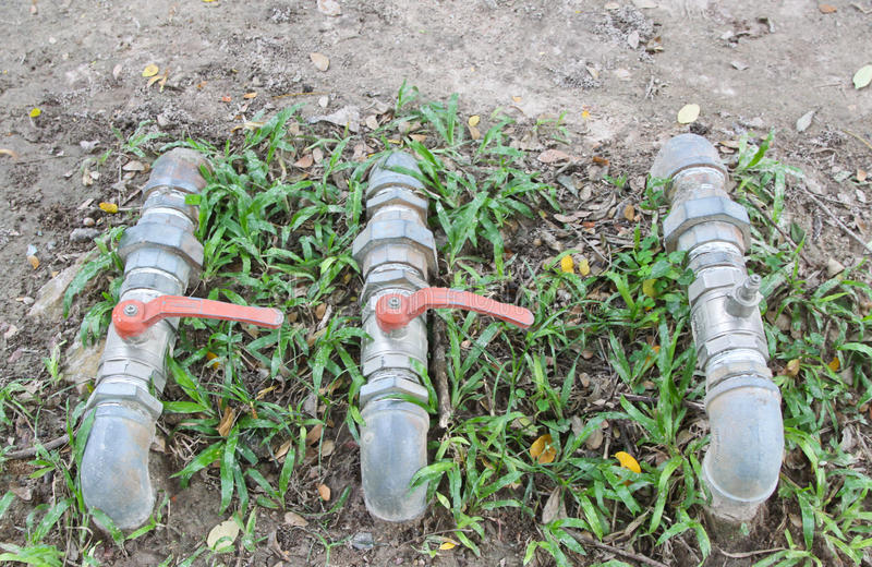 A water pipes on the green grass. Aqueduct, cargo, clear closet cold conduit delivering delivery drinking dryness duct farm faucet found fueling garden gardening royalty free stock photography