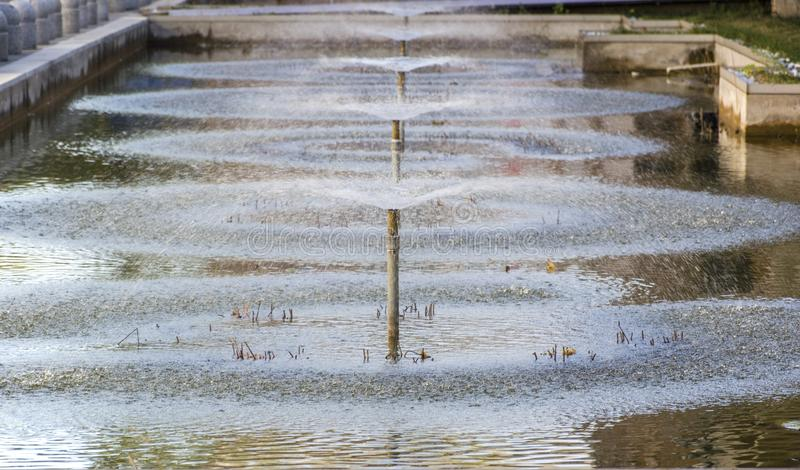 Fountain in the pond. Water pipes in the pond, spewing water stock photo