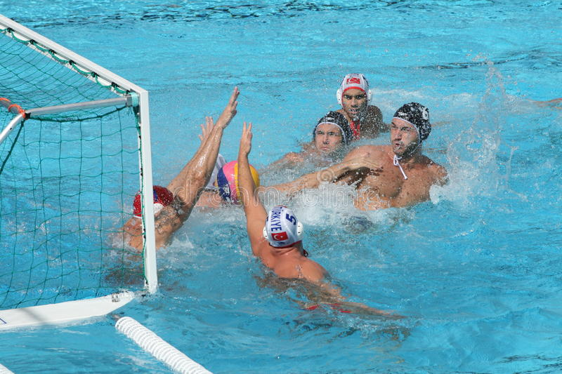 Water Polo / Panic In Front Of Goal. Turkish goalkeeper and two teammates panicky defending a goal while Romanian players tries to get a ball and put it into the royalty free stock photos