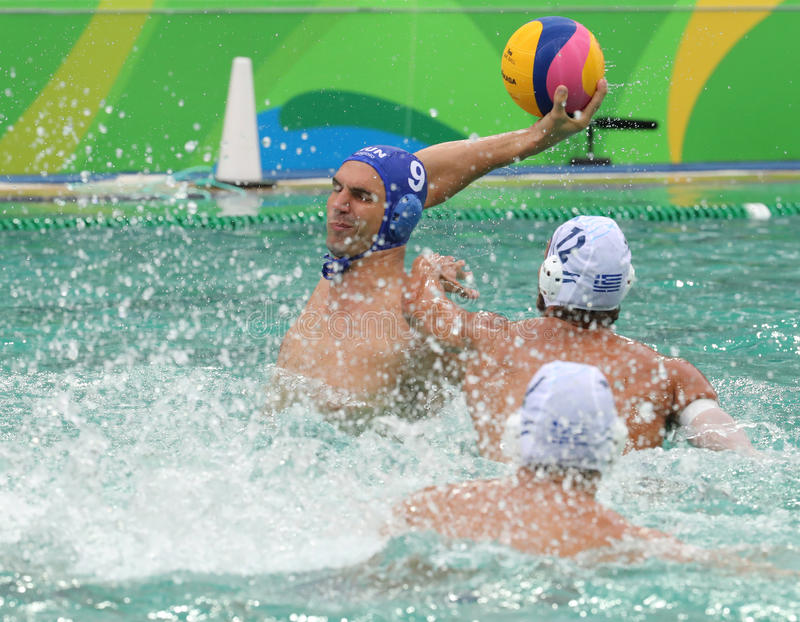 Water Polo Team Hungary in blue and Team Greece in action during Rio 2016 Olympics Men`s Preliminary Round Group A match. RIO DE JANEIRO, BRAZIL - AUGUST 10 stock image