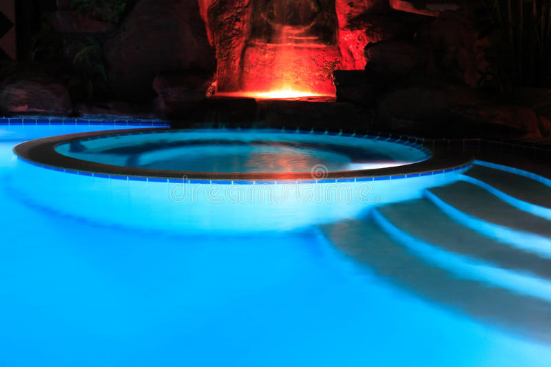 Water Pool At Night. Closeup of elegant empty water pool with blue water at night royalty free stock images