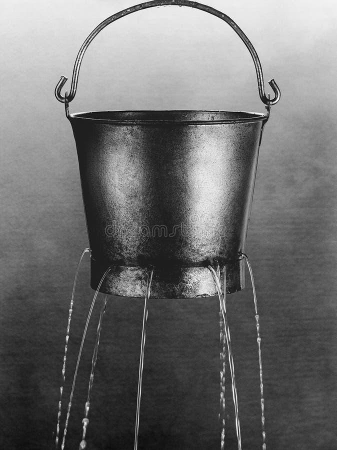 Water poring through holes in bucket (b&w) stock photo