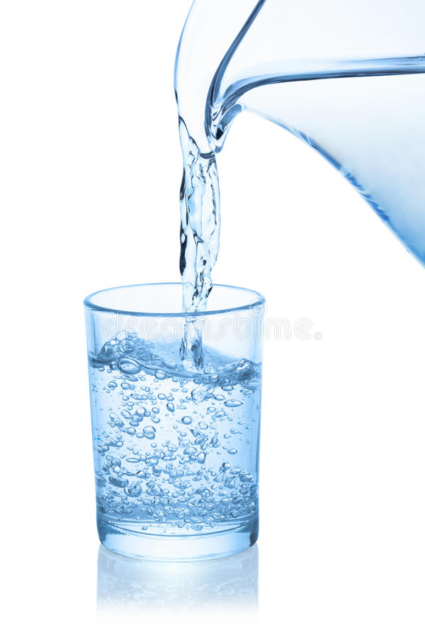 Water poured from the pitcher into a glass. Water poured from the pitcher into a glass, isolated on the white background, clipping path included royalty free stock photo