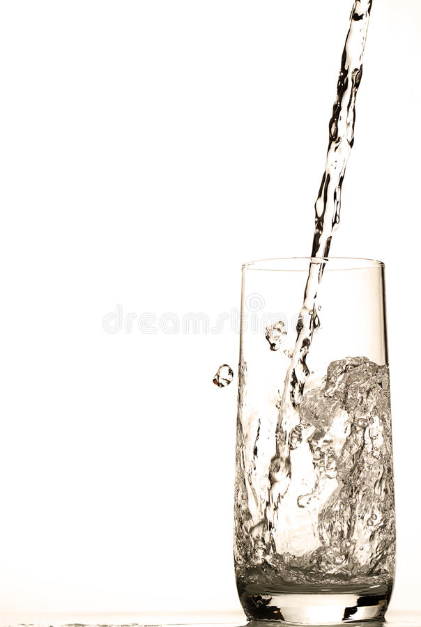 Water pouring in glass. Fresh water pouring in glass on white background royalty free stock images
