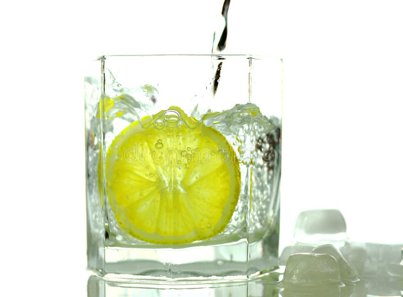Water pouring the glass with lemon stock photography